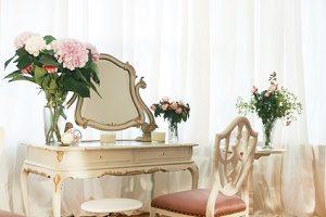 alter Schminktisch mit Stuhl und Blumen dekoriert