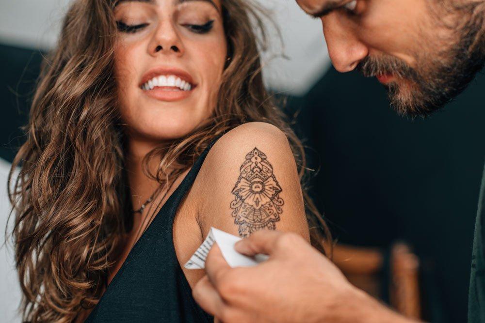 Mann macht Klebetattoo auf den Arm einer Frau