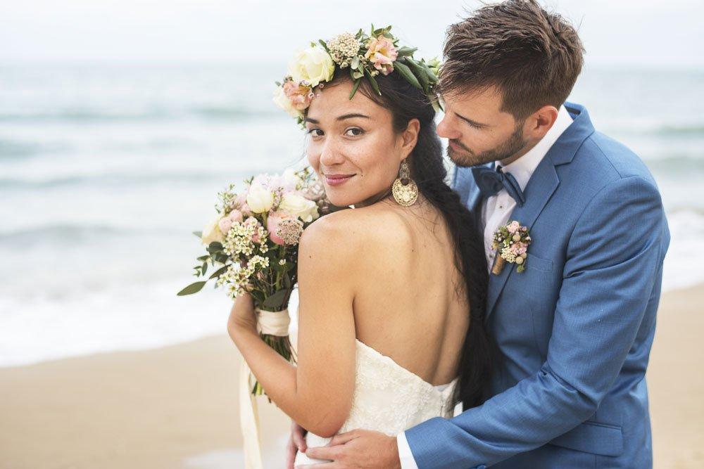 Brautpaar mit Blumenstrauß am Strand