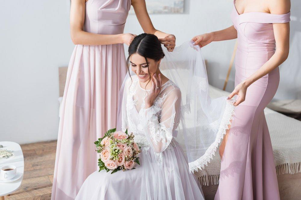 Brautjungfern richten Schleier der Braut