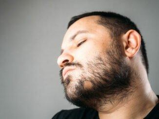 Mann hat kahle Stelle im Bart