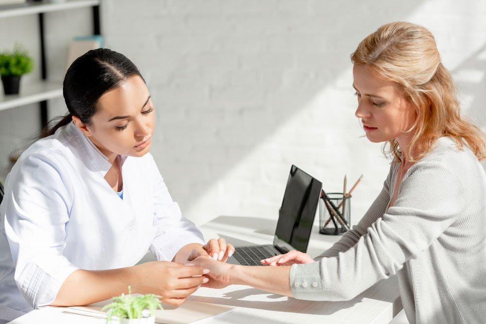 Hautärztin untersucht Hand