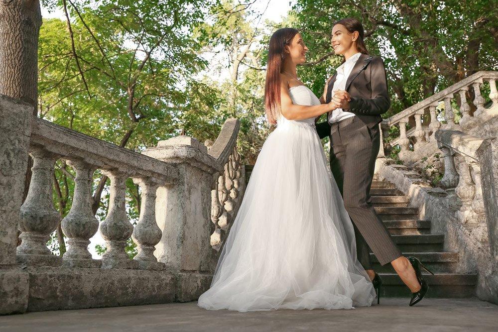 lesbische Hochzeit in Brautkleid und Anzug