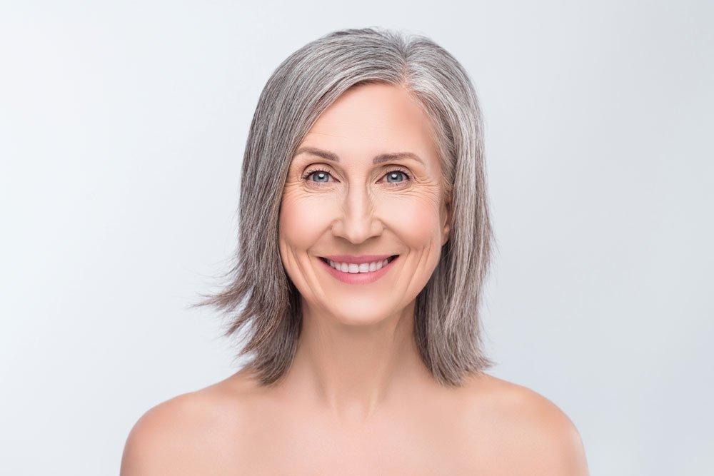 Frau mit grauen Haaren und Stufenschnitt